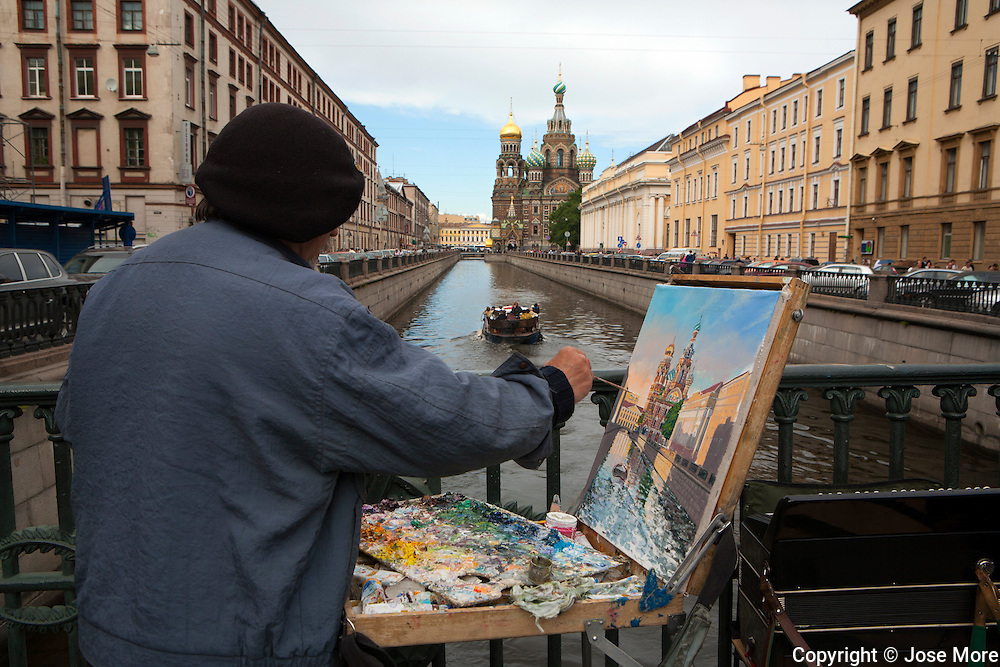A street artist paints the Church of Our Savior on Spilled Blood, a Russian-style church was built on the spot where Emperor Alexander II was assassinated in Saint Petersburg on March 1881. <br /> <br /> Photography by Jose More