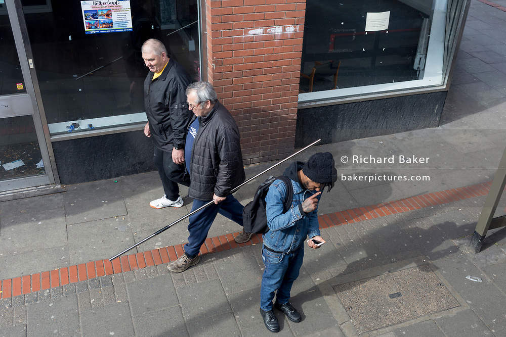 Aerial view of men on the Walworth Road in the south London borough of Southwark, on 25th March 2019, in London, England.