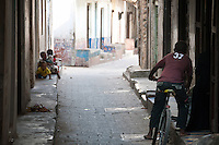 A boy riding his bicycle through Stone Town, Zanzibar, Tanzania