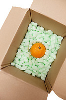 Open cardboard box with packing peanuts and orange in it