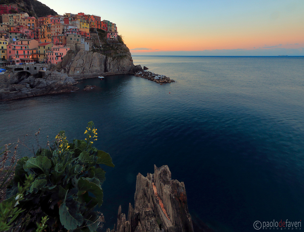 A view at dawn of the beautiful small fishermen village of Manarola, one of the five villages altogether known as Cinque Terre. Taken about 15 minutes before sunrise on a morning at the beginning of April.