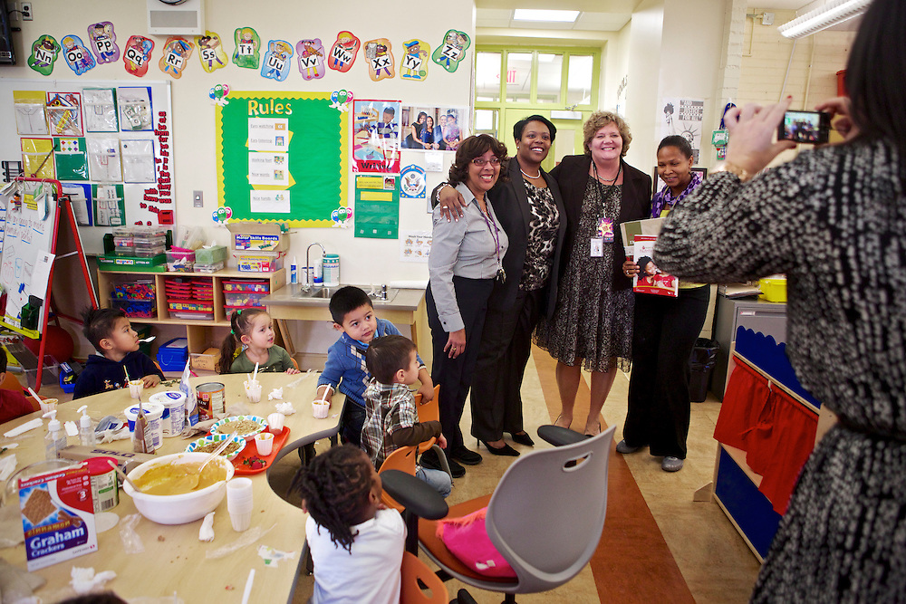 D.C. Public Schools Chancellor Kaya Henderson, fourth from the right, has her photo taken with Principal Mary Ann Stinton, third from right, and preschool teacher Tilwanda Law, center, at Truesdell Education Campus on Friday, Nov. 16, 2012 in Washington, D.C. Henderson recently announced that she plans to close 20 under-enrolled schools across the district. CREDIT: Lexey Swall for The Wall Street Journal