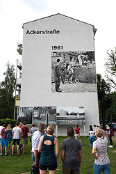 Mural painted on apartment building showing historic view of Berlin Wall at memorial park at Bernauer Strasse in Berlin, Germany