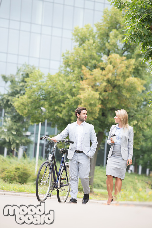 Businesspeople with bicycle conversing while walking on street