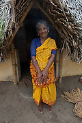 In a small fishing village called Patinacherry, a woman stands in the entrance to her thatched home.