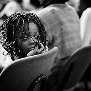 A young girl in the congregation at a Saturday afternoon service at Shekina Cathedral in Brussels, Belgium on 7 July 2012. Located in a converted warehouse space in a neighbourhood dominated by the secondhand car trade, the church has a predominantly Congolese congregation, most of whom do not live in the neighbourhood but who come each week to attend church.