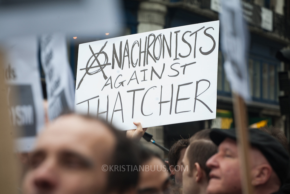 "The funeral of former Prime Minister Margaret Thatcher who died Monday April 8. A protester against the publicly funded funeral and Thatcher's policies hold up a plackard which reads: ""Anachronists against Thatcher"""