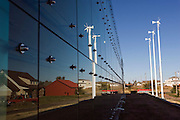 "Greensburg, Kansas, USA..Reflexion of the art centers three wind turbines in the glass panels of 5.4.7 Art Center..The 5.4.7 Arts Center takes their name from the date of the tornado that devastated Greensburg on May 4, 2007. It is the first LEED Platinum building designed and constructed by students, and is the first LEED Platinum certified structure in the state of Kansas. The building earned the LEED Platinum certification through its use of wind turbines, photovoltaic panels, geothermal climate control, recycled building materials and a host of other ecologically minded features. The 5.4.7 Art Center is a community arts center to raise awareness of fine arts, both visual and performing, making arts accessible to everyone and provide an environment to create and gather knowledge through classes, exhibits and performances. ""The arts are extremely important to our community in order to maintain and cultivate our identity, our heritage, and our culture.""..""Greensburg: Better, Stronger, Greener!"".On May 4, 2007, an EF5 tornado cut a 1.7-mile path of destruction through Greensburg, Kansas. Winds reaching speeds of 205 miles per hour uprooted trees, demolished homes and leveled the town. Eleven people died and 95% of the buildings were destroyed beyond repair. Residents have since worked furiously to rebuild it in a way that is both economically and environmentally sustainable and to meet the highest environmental standards. Greensburg, whose population has dropped from about 1400 to 800 following the storm and is now growing again, is currently the greenest town in America and the first in the United States to pass a resolution to certify that all city-owned buildings earn LEED Platinum accreditation, the highest level of the LEED rating system...Foto © Stefan Falke"