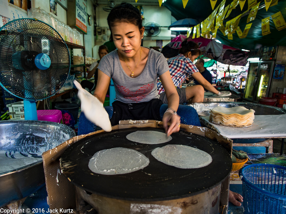"12 JANUARY 2016 - BANGKOK, THAILAND: Women make ""roti,"" a type of grilled flat bread, in Khlong Toey Market in Bangkok. Khlong Toey (also called Khlong Toei) Market is one of the largest ""wet markets"" in Thailand. Roti is originally from India and came to Thailand via Indian immigrants who settled in Thailand in the 1800s. The market is located in the midst of one of Bangkok's largest slum areas and close to the city's original deep water port. Thousands of people live in the neighboring slum area. Thousands more shop in the sprawling market for fresh fruits and vegetables as well meat, fish and poultry.         PHOTO BY JACK KURTZ"