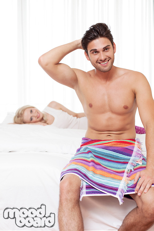 Shirtless young man smiling with woman in background at hotel room