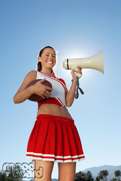 Cheerleader Holding Football and Megaphone