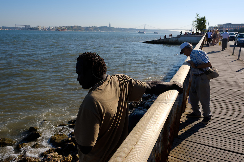 People  by the Tagus riverside. Terreiro do Paço, the largest Lisbon square, and is one of the most well-know place to visit in Lisbon.