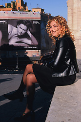 Europe, Italy, Rome, woman wearing leather jacket on stone wall near sexy billboard