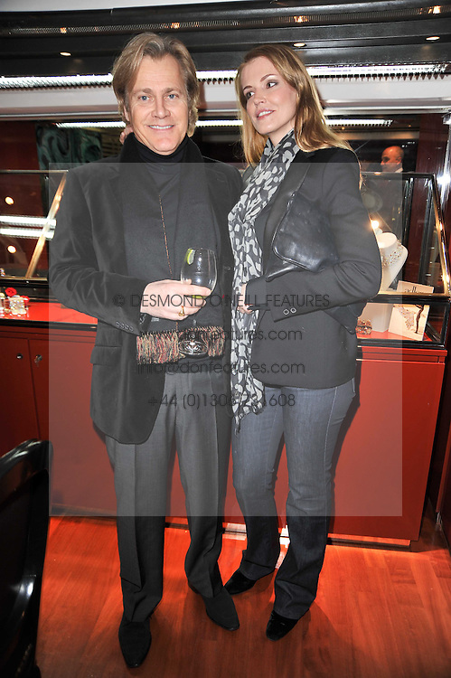 Actor RICHARD RAYNESFORD and designer CATIOUCHE (Lana Berglas) at a party to view jewellery by Adler and paintings by Marie Guerlain held at Adler, 13 New Bond Street, London W1 on 9th February 2011.