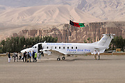 Pilot, Danielle Aitchison, and her partner Captain Chris Hood stand next to their aircraft with the Bamiyan Buddhas in the background.  ..Passengers wait to board the UNHAS flight on the remote Bamiyan air field.  The airstrip is made of rocks and gravel and not entirely straight, making take off and landings more challenging in the remote mountins...