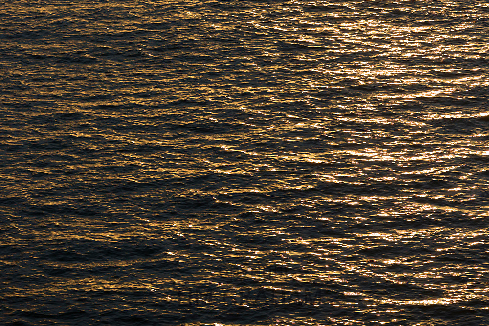 Sun on water - close up of ripples, gentle waves and sunlight reflecting on the surface of the ocean