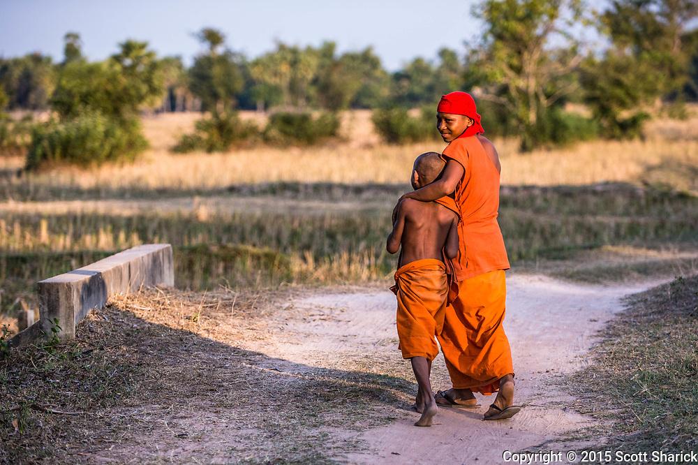 Two novice Monks walk down a dirt pathway near Kouk Trach, Cambodia