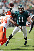 Philadelphia Eagles quarterback Carson Wentz (11) scrambles as he regains his balance and throws a late second quarter pass despite pressure from Cleveland Browns linebacker Nate Orchard (44) in the second quarter during the 2016 NFL week 1 regular season football game against the Cleveland Browns on Sunday, Sept. 11, 2016 in Philadelphia. The Eagles won the game 29-10. (©Paul Anthony Spinelli)