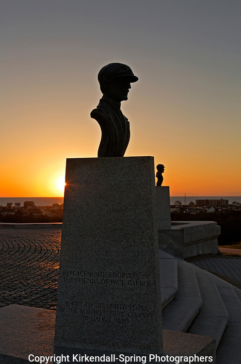 NC01435-00...NORTH CAROLINA - Sunrise at the busts of the Wright brother at the monument commemorating the site of their first flight at Kitty Hawk on the sand dunes of the Outer Banks.