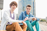 Portrait of young male college students studying on steps against building
