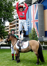 Frankie Dettori watches his son Rocco dismount during a media day at Ascot Racecourse, Esher.