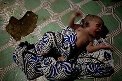 A new born baby lies on the floor at the home of a midwife in Mathare, a poor slum in Nairobi, Kenya.  Most women in Mathare can not afford to go to a hospital to give birth; they can not even afford the 10 minute taxi ride to get there.  The expecting mothers have no prenatal care and arrive to the midwives' homes once labor has already begun.  The midwives have no supplies and are usually have no formal training.  The mothers often give birth on dirt floors with no medicine, and their babies' unbilical cords are cut with dirty scissors and they are washed with tap water.