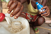 A woman uses a chlorine water treatment product to treat drinking water at home in the village of Kawejah, Grand Cape Mount county, Liberia on Friday April 6, 2012. As part of the UNICEF sponsored CLTS programme, communities learn to put in practice good hygiene and sanitation practices.
