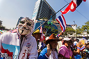 "13 JANUARY 2014 - BANGKOK, THAILAND:  An anti-government protestor  with a Guy Fawkes mask in front of MBK shopping center in Bangkok. Many of the protestors wear Guy Fawkes masks, inspired by the movie V for Vendetta. Tens of thousands of Thai anti-government protestors took to the streets of Bangkok Monday to shut down the Thai capitol. The protest was called ""Shutdown Bangkok"" and is expected to last at least a week. The Shutdown Bangkok protest is a continuation of protests that started in early November. There have been shootings almost every night at different protests sites around Bangkok, including two Sunday night, but the protests Monday were peaceful. The malls in Bangkok stayed open Monday but many other businesses closed for the day and mass transit was swamped with both protestors and people who had to use mass transit because the roads were blocked.   PHOTO BY JACK KURTZ"