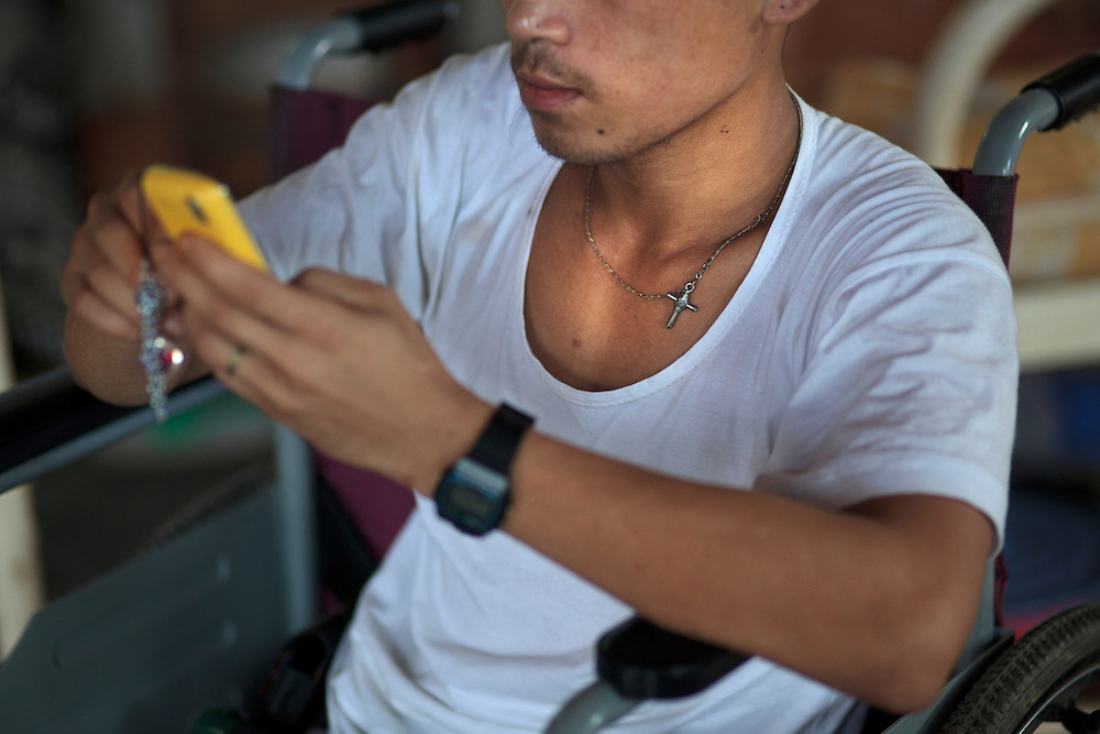 Kachin's militia member Lalaw Ze Dai, from Waimaw village, 25, play with his phone in the General Military Hospital in Laiza village close to the China border, Myanmar on July 19, 2012.  He was injured by a landmine in June, 26, 2012 loosing part of his right leg on top of knee.