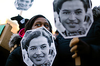 Boston, MA - Acacia Johnson-Bowden a high school student in Boston listens to a speaker while holding up a cut out mask of civil rights icon Rosa Parks at a protest of the proposed fare hikes and service cuts by the MBTA in front of the Boston Public Library on Copley Square on Monday, February 13, 2012.  Photo by Matthew Healey