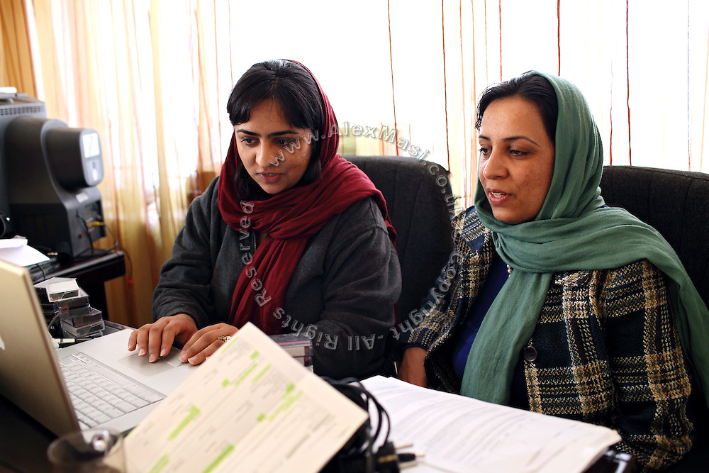 Roya Sadat, 28, (right) and Alka Sadat, 24, (centre), two sisters working on documentary and fiction film, are sitting at their desk while editing part of their recent shooting in their home in Kabul, Afghanistan.