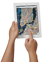Person holding an Apple iPad2 in their hands using the Maps application and photographed on a white background.