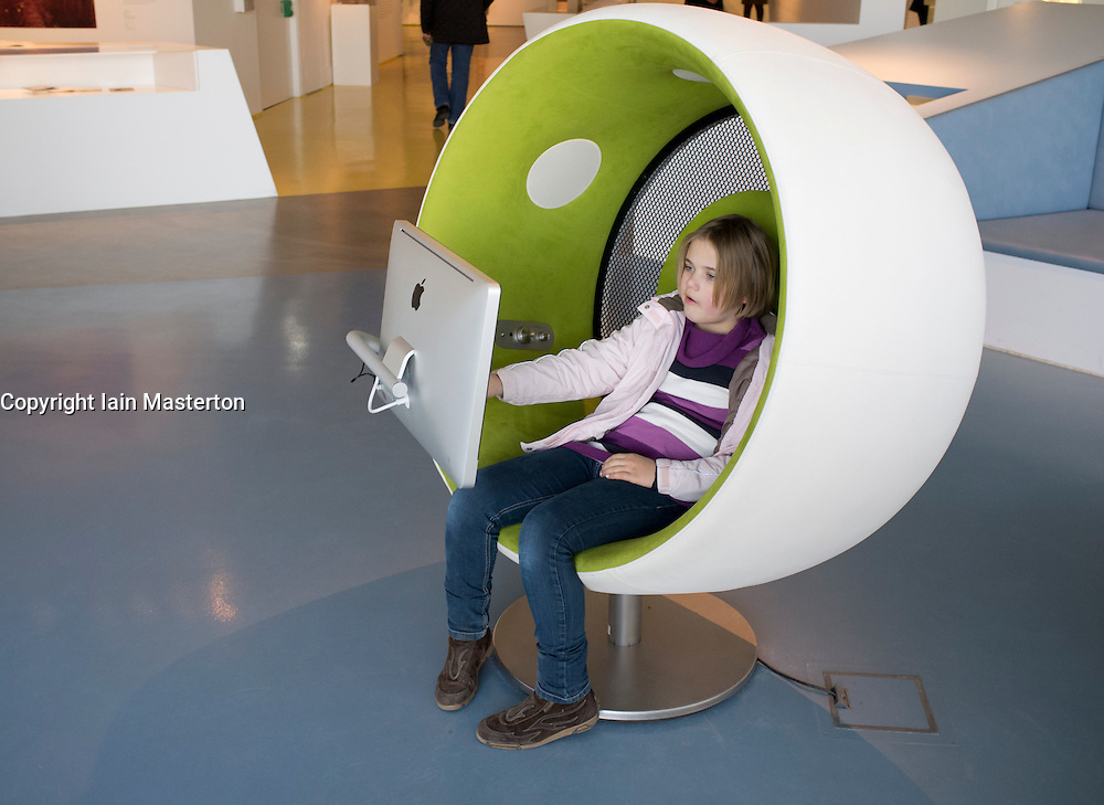 Young girl visitor using multimedia area at Humboldt Box visitors center at Lustgarten on Unter den Linden Mitte Berlin