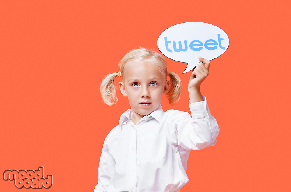 Portrait of a young girl holding tweet bubble against orange background