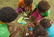 Kids in Lobo Village race to complete puzzles depicted the marine protected areas designated by Triton Bay communities. A Bryde's Whale provides pointers.