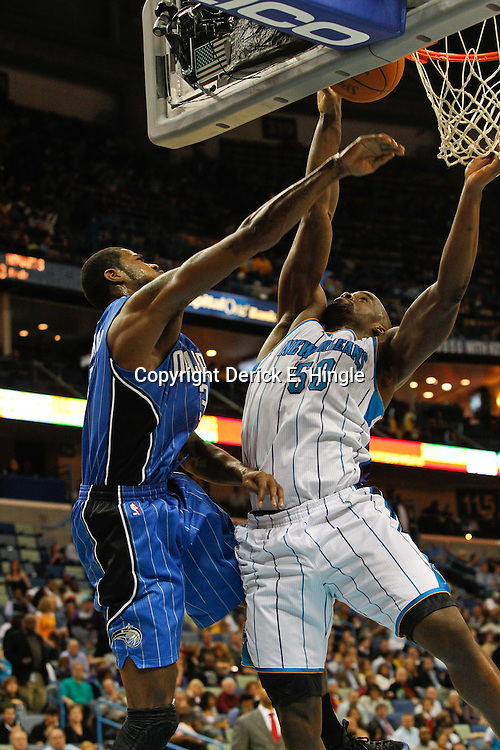 January 27, 2012; New Orleans, LA, USA; New Orleans Hornets center Emeka Okafor (50) blocks a shot by Orlando Magic forward Earl Clark (3) during a game at the New Orleans Arena. The Hornets defeated the Magic 93-67.  Mandatory Credit: Derick E. Hingle-US PRESSWIRE
