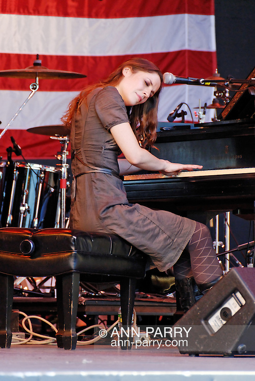 East Meadow, NY - OCTOBER 15: Katy Pfaffl, singing and playing piano, with stripes of large American flag seen on wall behind her, during Obama Rally at Eisenhower Park October 15, 2008 in East Meadow, New York, less than 2 miles away from Hofstra University, the site of final presidential debate held later that night.