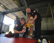Firemen John Cullen (left) and John Levy (right) help Tyler Rucker into a small fire suit as Bramlett Elementary students visit the Oxford Fire Department to learn about fire safety in Oxford, Miss. on Monday, October 18, 2010.