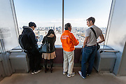 A volunteer tourist guide (in orange jacket) guides a British tourist around the 45th floor Observation deck of the Tokyo Metropolitan Government Tower Shinjuku, Tokyo, Japan. Tuesday November 29th 2016.