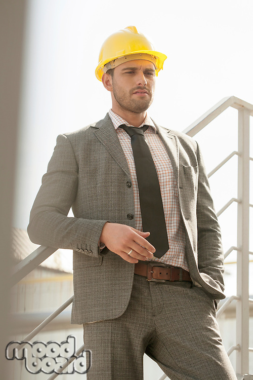 Young male architect in hard hat leaning on railing against clear sky