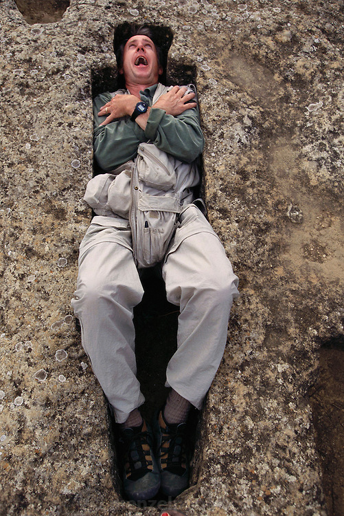 Peter Menzel lying down in the rock tombs from Roman times on the grounds of the Remelluri Winery Labastida, La Rioja, Spain.  MODEL RELEASED.