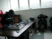 Teenager DJ'ing to a group of friends in a hall, UK, 2000's