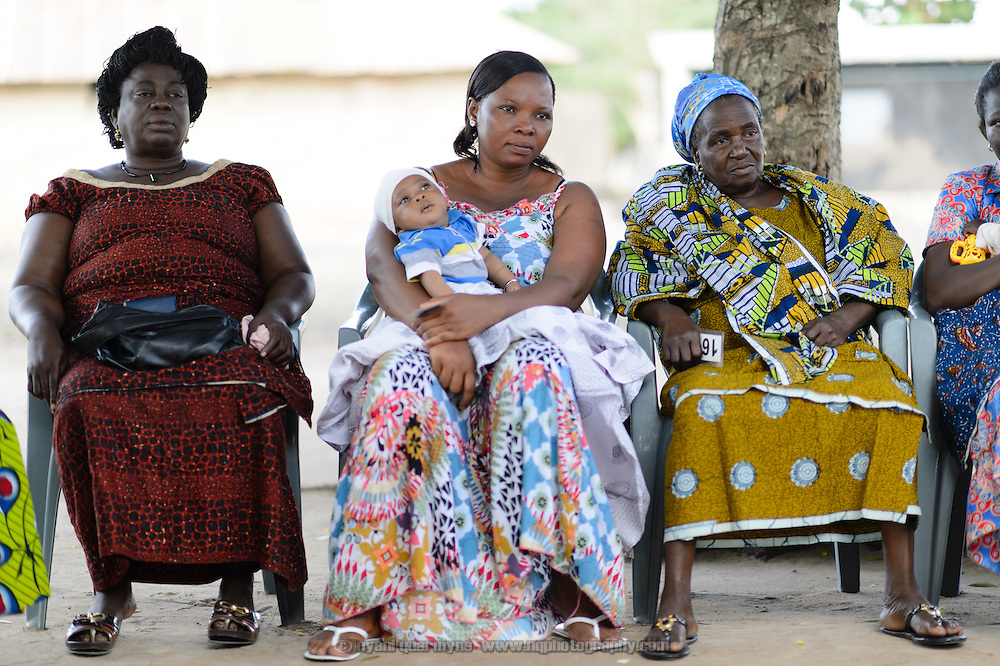 Selina Diaba (left), Charity Affu and her son Elikem Kortsu, and Mary Kpordewu at a 'Banking on Change' Village Savings and Loan Association (VSLA) meeting at Dabala Junction in the Volta Region of Ghana on 12 September 2012. Members contribute savings weekly and receive a payout commensurate with their inputs at the end of each year. Members may also access small loans, which many use to support entrepreneurial activities, and they make small insurance contributions which may be drawn upon in the event that an individual member has a financial emergency.