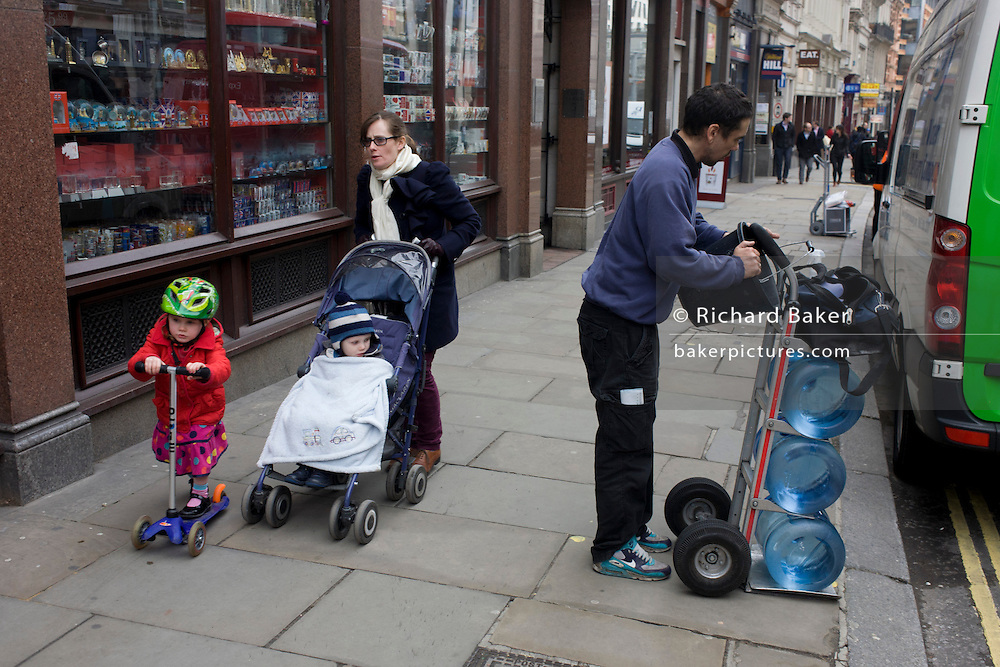 Mother and children pass a delivery man and bottles of office drinking water in City street.