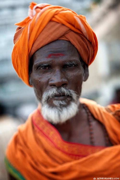 A sadhu stands outside of a Shiva temple and awaits alms in the venerated town of Thiruvannamalai, Tamil Nadu, India. Sadhus are renunciates who have abandoned all material and sexual attachments to live in caves, forests and temples all over India in the pursuit of Moksha (liberation). December 28, 2007