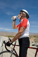 Senior man with bike drinking water