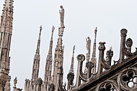 Milan, Italy, Duomo Cathedral. Rooftop spires topped by statues and ornamental stonework in the foreground.