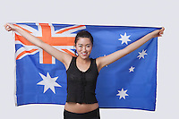 Portrait of smiling young woman holding Australian flag over white background