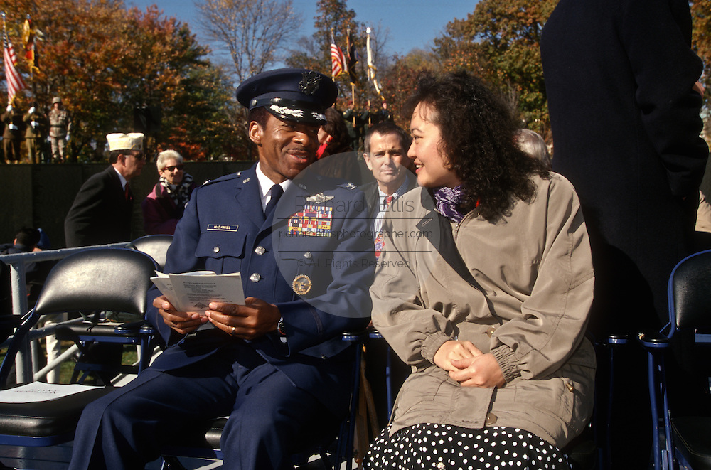 Phan Thi Kim Phuc, a napalm victim pictured in a Pulitzer Prize-winning 1972 photo by Nick Ut speaks with Vietnam War POW Air Force Col. Norm McDaniel during a Veterans Day ceremony at the Vietnam Veterans Memorial November 11, 1996 in Washington, DC.