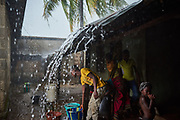 A family collects water during a storm in Kenema District, Sierra Leone on June 6, 2017.